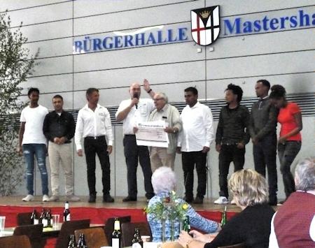 Joachim Lehnert vom Sportverein überreicht der Flüchtlingshilfe eine Spende